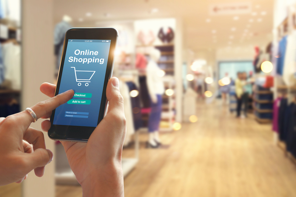 Smart phone online shopping in woman hand. Network connection on mobile screen. Payments online. Shopping mall department store background