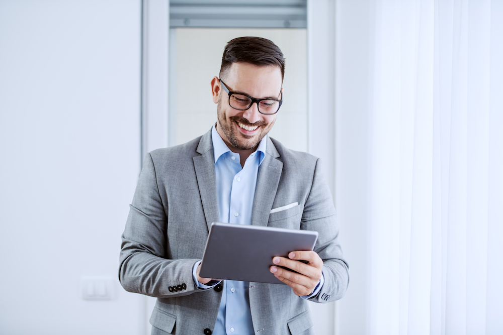 Attractive cheerful caucasian classy businessman in suit and with eyeglasses holding tablet and standing next to window.