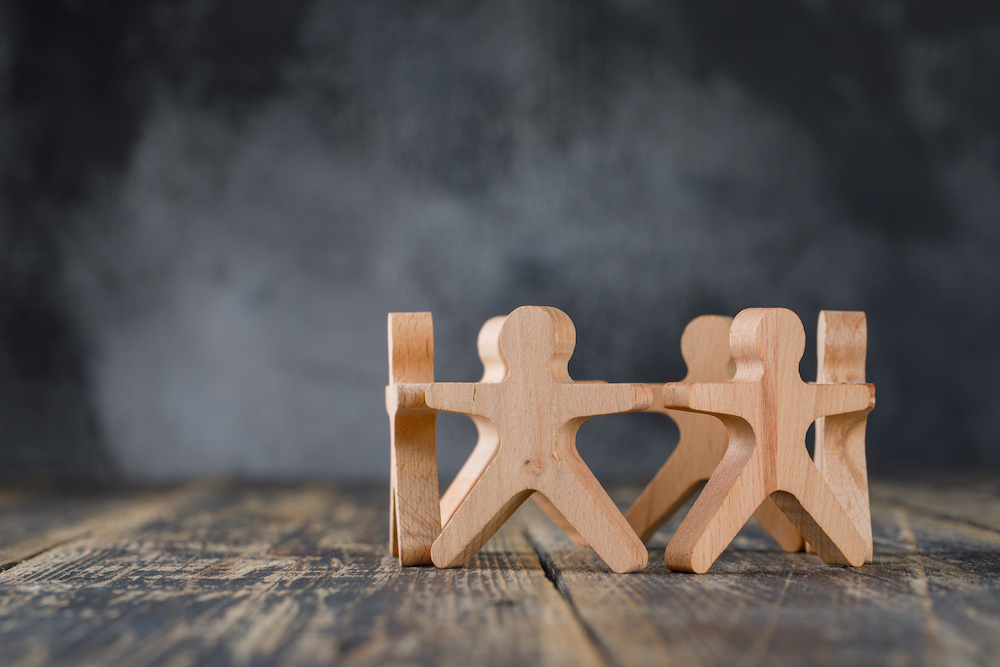 Business success and teamwork concept with wooden figures of people on wooden and foggy background side view.