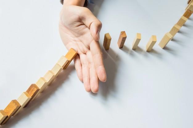 empresario-mano-parada-domino-continua-derribado-o-riesgo-copyspace_1423-17