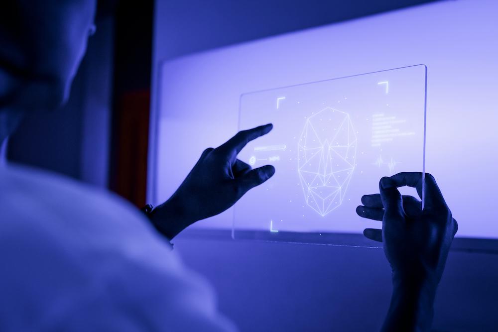 Designer using a transparent digital tablet screen futuristic technology